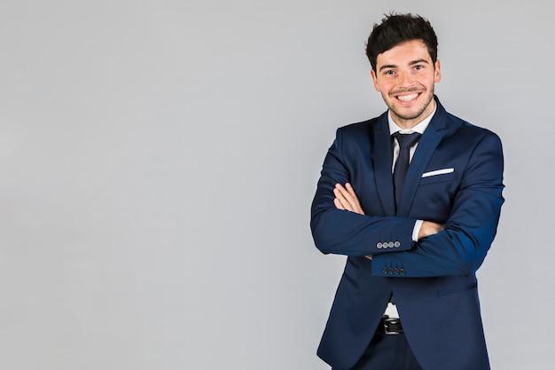 Portret van een zelfverzekerde jonge zakenman met zijn arm gekruist staande tegen een grijze achtergrond