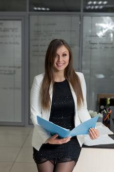 Portret van een zelfverzekerde jonge zakenvrouw die een dossier op kantoor houdt.
