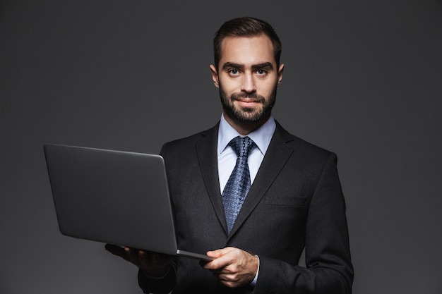 Portret van een zelfverzekerde knappe zakenman die een kostuum draagt dat zich geïsoleerd bevindt, laptop computer vasthoudt