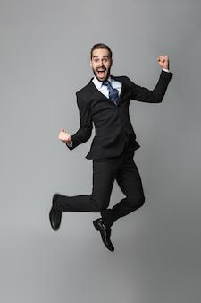 Portret van een zelfverzekerde knappe zakenman die geïsoleerd kostuum draagt, het springen, succes viert