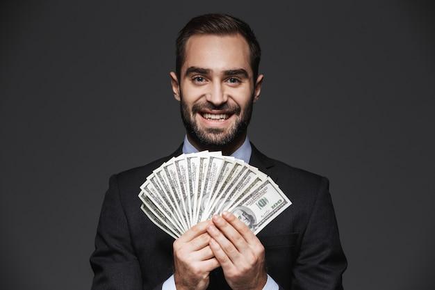 Portret van een zelfverzekerde knappe zakenman die geïsoleerd pak draagt, dat geldbankbiljetten toont