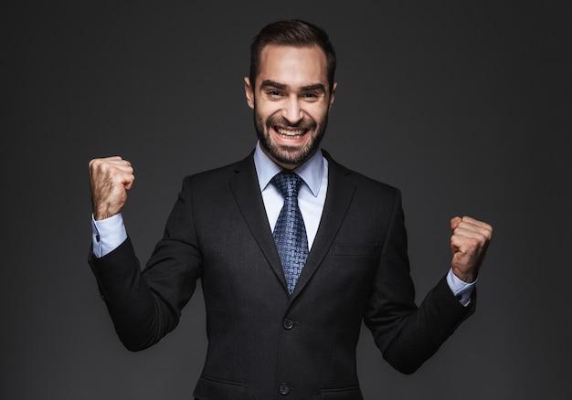 Portret van een zelfverzekerde knappe zakenman die geïsoleerde kostuum draagt, die succes viert