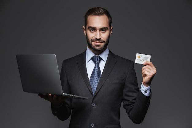 Portret van een zelfverzekerde knappe zakenman die geïsoleerde kostuum draagt, laptop computer houdt, die creditcard toont