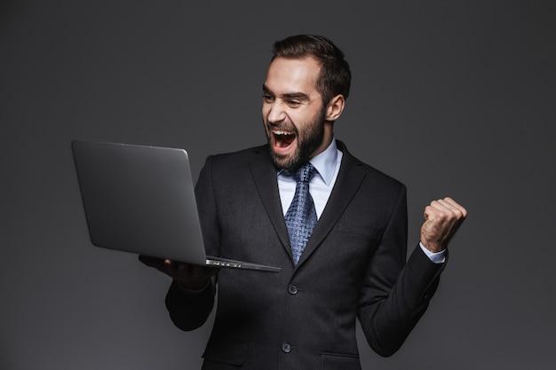 Portret van een zelfverzekerde knappe zakenman die geïsoleerde kostuum draagt, laptop computer houdt, die succes viert