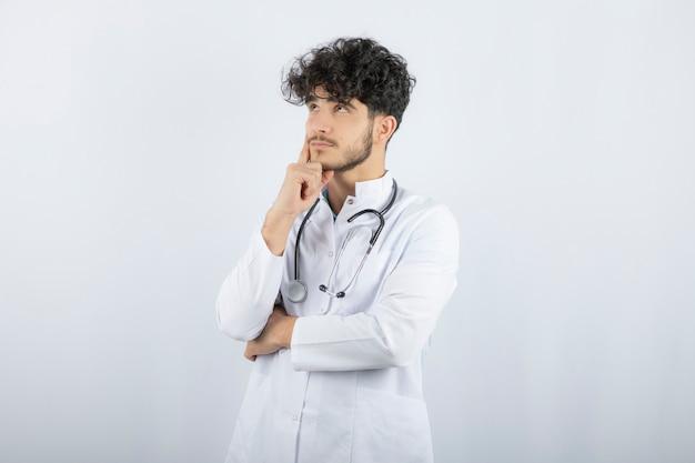 Portret van een zelfverzekerde mannelijke arts die op wit wordt geïsoleerd.