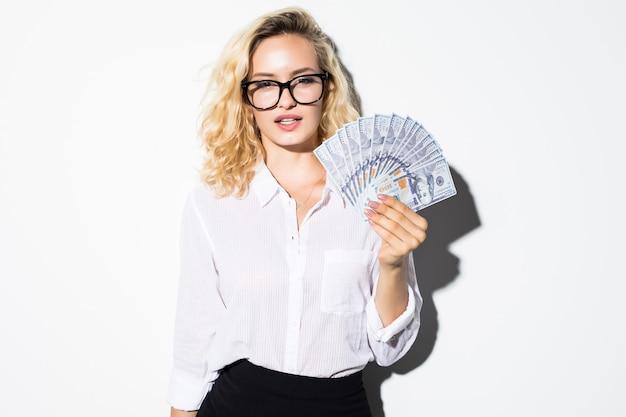 Portret van een zelfverzekerde onderneemster die een hoop geldbankbiljetten toont die over witte muur worden geïsoleerd