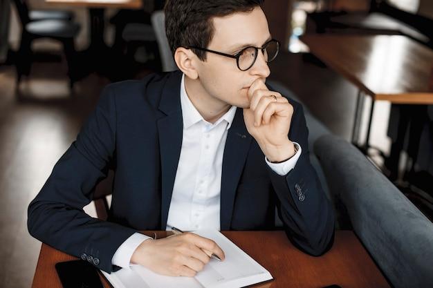 Portret van een zelfverzekerde serieuze manager die een bril draagt die serieus kijkt op het laptopscherm terwijl hij een hand op zijn lippen houdt, een andere op de notebook.