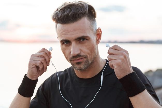 Portret van een zelfverzekerde sportman, luisteren naar muziek close-up