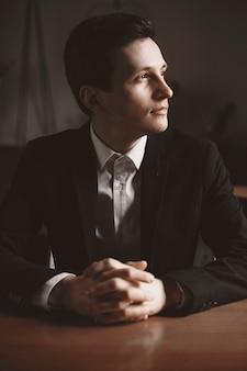 Portret van een zelfverzekerde volwassen zakenman wegkijken door het raam met de hand op de tafel zittend in een café.
