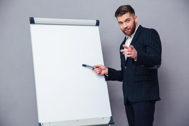 Portret van een zelfverzekerde zakenman die iets op een leeg bord over grijze muur presenteert