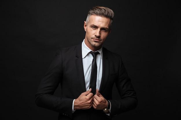 Portret van een zelfverzekerde zakenman gekleed in een formeel pak die zijn jas aanraakt en naar een camera kijkt die over een zwarte muur is geïsoleerd