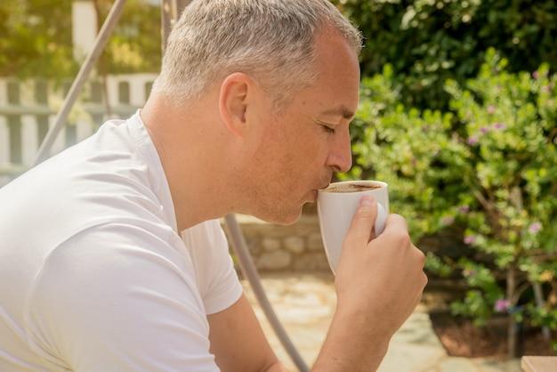 Portret van een zelfverzekerde zakenman op de bank zitten en koffie buiten drinken. zakenman drinken koffie in de tuin. vintage toon.