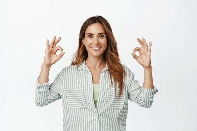 Portret van een zelfverzekerde zakenvrouw die gelukkig glimlacht en een goed ok-teken laat zien als goedkeuring