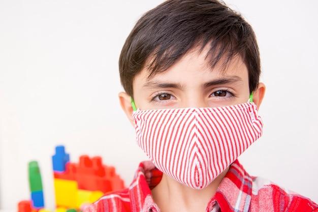 Portret van een zesjarig jong geitje dat gezichtsmasker draagt en beschermt tegen pandemie covid-19 virus pandemie