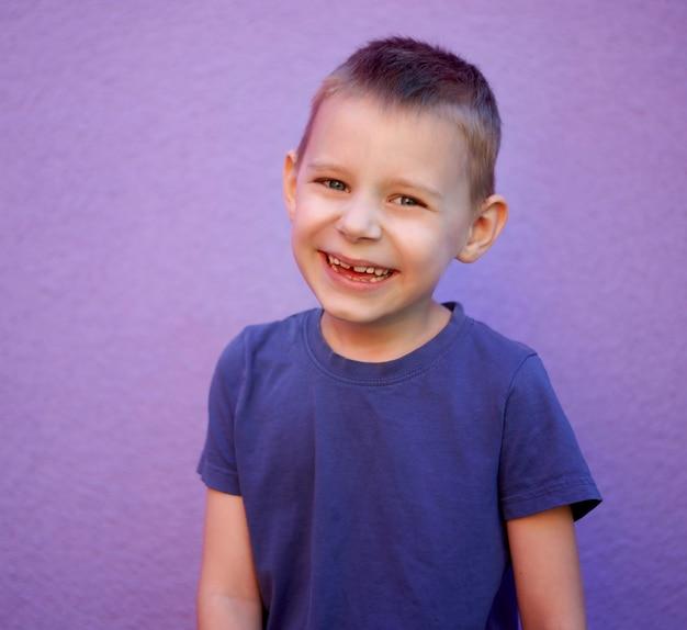 Portret van een zesjarige lachende jongen in een blauw t-shirt op een paarse achtergrond