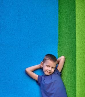 Portret van een zesjarige lachende jongen in een blauw t-shirt tegen de achtergrond van de muur van groen en blauw