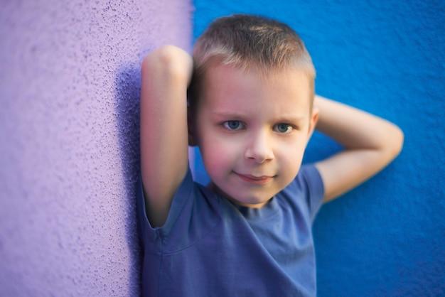 Portret van een zesjarige lachende jongen in een blauw t-shirt tegen de achtergrond van de muur van violet en blauw