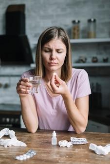 Portret van een zieke jonge vrouw met een glas water en medicijnen