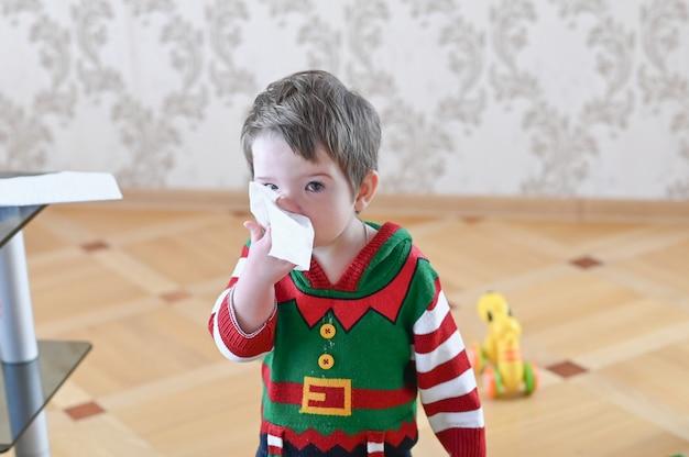 Portret van een zieke jongen die zijn neus met een servet schoonmaakt