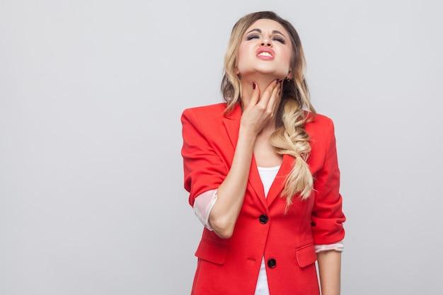 Portret van een zieke, mooie zakenvrouw met kapsel en make-up in een rode mooie blazer die staat, haar nek aanraakt en keelpijn voelt. indoor studio opname, geïsoleerd op een grijze achtergrond.