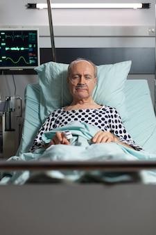 Portret van een zieke oudere man die in een ziekenhuisbed rust, ademt met behulp van een zuurstofmasker vanwege een longinfectie