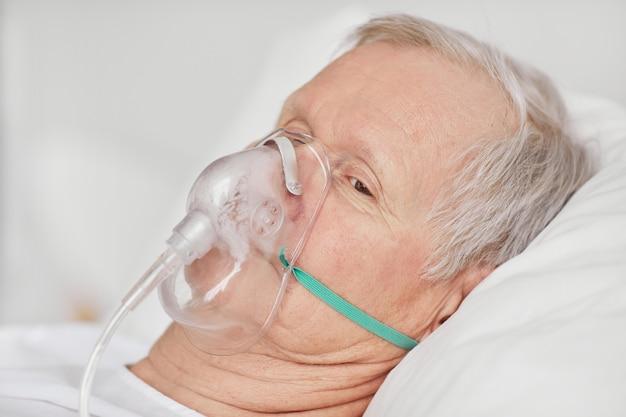 Portret van een zieke senior man die in het ziekenhuisbed ligt met een zuurstofmasker en peinzend wegkijkt, kopieer ruimte