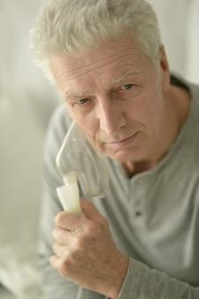 Portret van een zieke senior man met inhalator