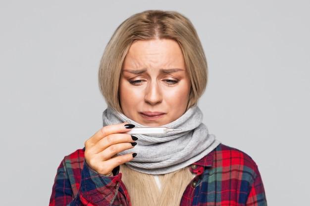 Portret van een zieke vrouw die de thermometer bekijkt om haar temperatuur te controleren