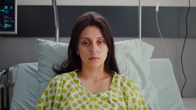 Portret van een zieke vrouw die een neuszuurstofbuis draagt die in bed rust