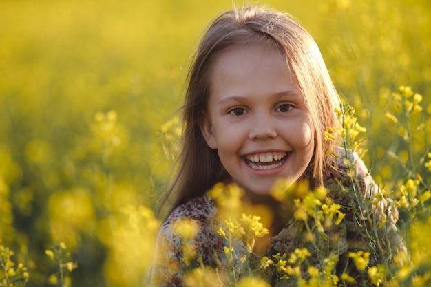 Portret van een zorgeloos jong meisje dat van de zonsondergang op een canolagebied geniet