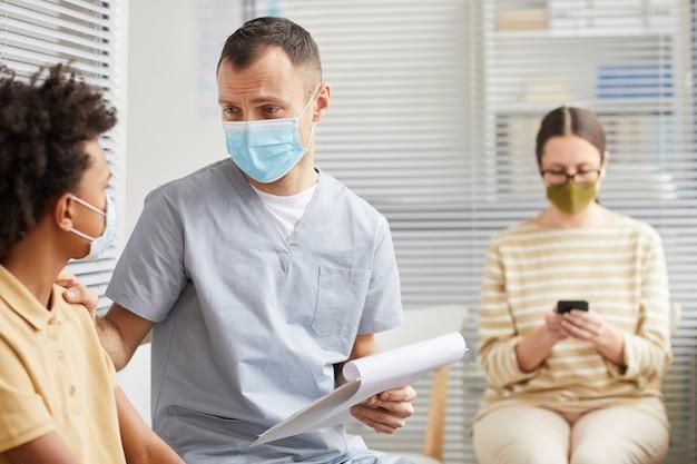 Portret van een zorgzame mannelijke arts die praat met een jongen die in de rij staat te wachten in de medische kliniek, beide met maskers, kopieer ruimte