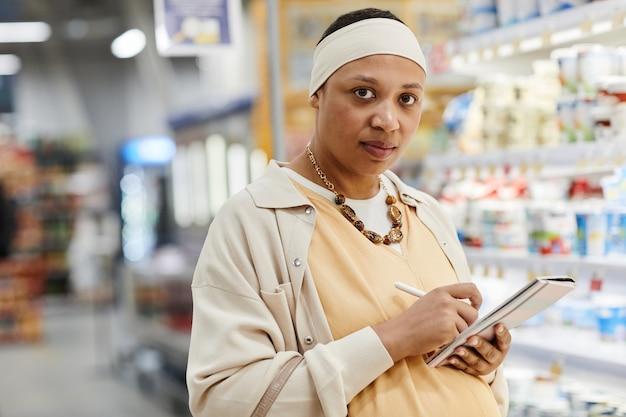 Portret van een zwangere afro-amerikaanse vrouw die boodschappen doet in de supermarkt en naar de camera kijkt, kopieer ruimte