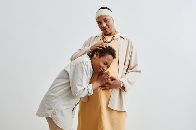Portret van een zwangere afro-amerikaanse vrouw met een gelukkige tienerzoon die zich voordeed tegen een witte achtergrond, kopieer ruimte