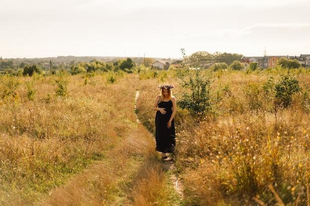 Portret van een zwangere vrouw een mooie jonge zwangere vrouw in een witte jurk loopt in het veld