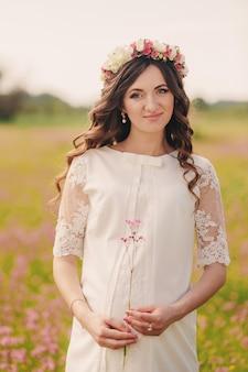 Portret van een zwangere vrouw op gebied van roze wilde bloemen. mooie zwangere meisje met een krans van bloemen op haar hoofd in de zon. moederschap. de lente. kopieer ruimte. selectieve aandacht.