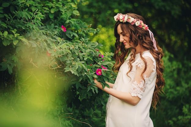 Portret van een zwangere vrouw op groene natuur muur. mooie zwangere meisje met een krans van bloemen op haar hoofd. moederschap. de lente. kopieer ruimte. selectieve aandacht.