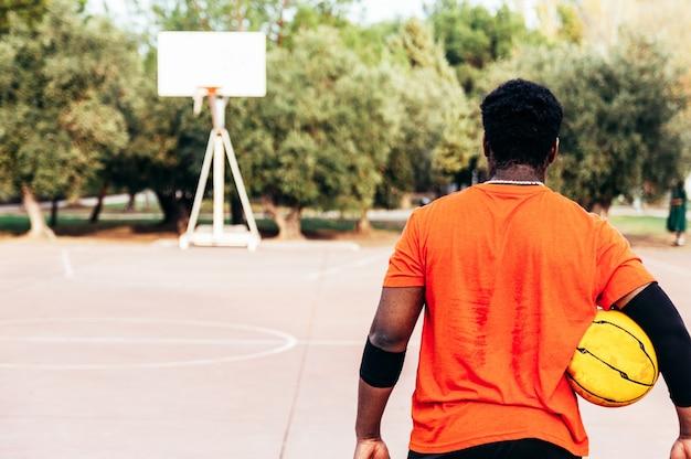 Portret van een zwarte afro-jongen die naar de mand op een stedelijk basketbalveld loopt.