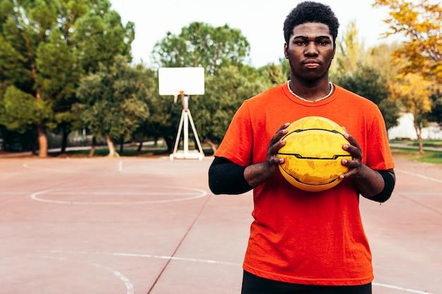 Portret van een zwarte afro-jongen met een uitdagende blik en een basketbal in zijn hand. klaar om een spel te spelen.