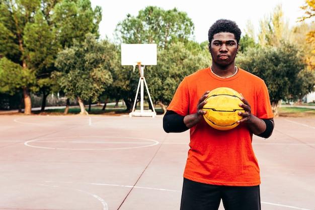 Portret van een zwarte afro-jongen met een uitdagende blik en een basketbal tussen zijn handen. klaar om een spel te spelen.
