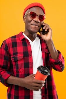 Portret van een zwarte amerikaanse knappe modieuze mens die een geruit roodachtig overhemd draagt dat een koffiepauze van de drankkop met een gele telefoon houdt