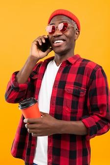 Portret van een zwarte amerikaanse knappe stijlvolle man met een geruit roodachtig shirt met een glas drinken op een koffiepauze en praten over de telefoon op een geel
