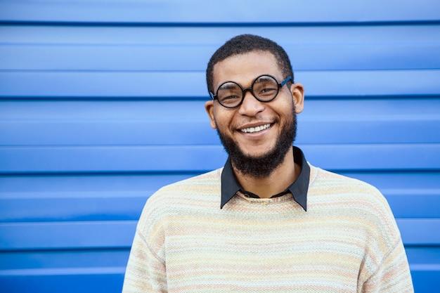 Portret van een zwarte man met ronde nerd bril, glimlachend. een blauwe straatmuur op de achtergrond.