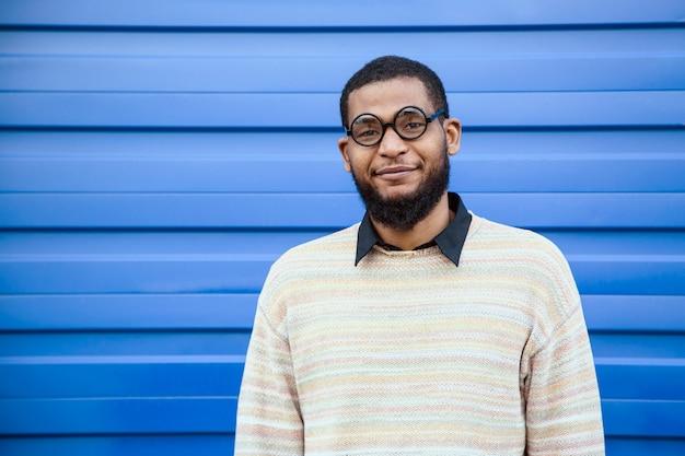 Portret van een zwarte man met ronde nerdglazen. een blauwe straatmuur op de achtergrond.