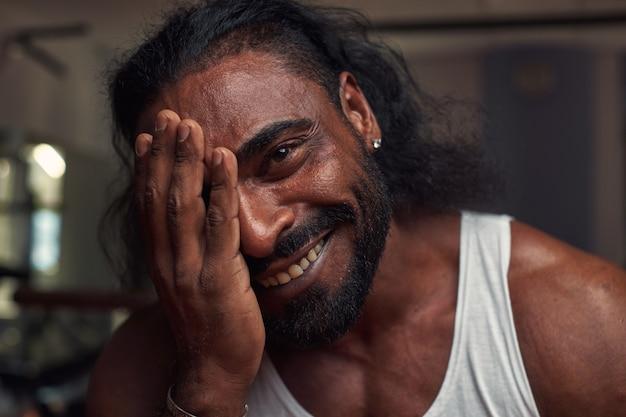 Portret van een zwarte mannelijke atleet met een gaatje in het oor die lacht en direct in de camera kijkt hi...