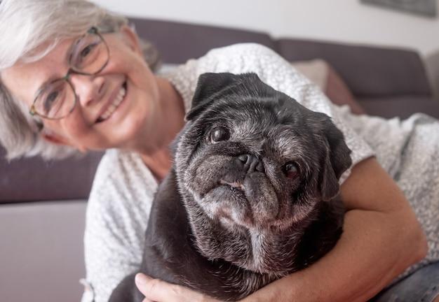 Portret van een zwarte oude mopshond die met zijn oudere eigenaar op de vloer thuis zit beste vriend concept