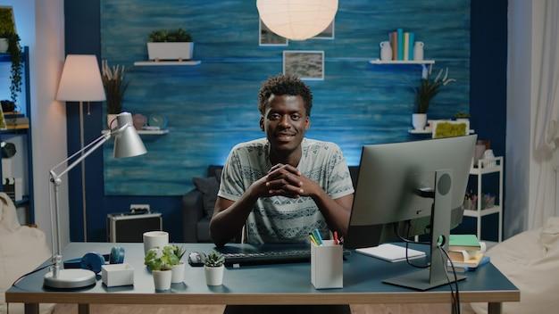 Portret van een zwarte volwassene die aan een bureau zit met een computer