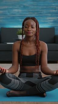 Portret van een zwarte vrouw die in de lotuspositie op de vloer zit en een ochtendademhalingsoefening doet