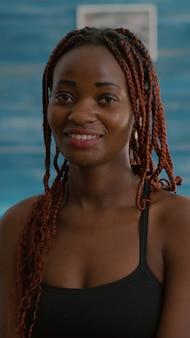Portret van een zwarte vrouw die lacht en in de camera kijkt tijdens de ochtendtraining van de fitness, zittend op je...
