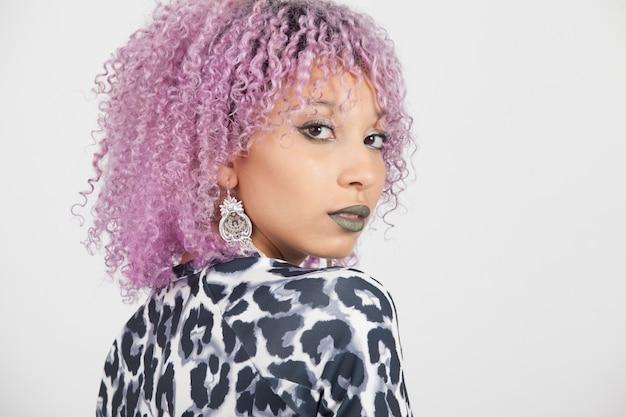 Portret van een zwarte vrouw met elegante oorbellen, sensuele blauwe lippen en paars afrohaar