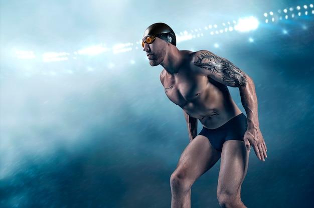 Portret van een zwemmer op een sportarena. atleet bereidt zich voor op de sprong.